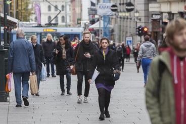 Mennesker går opp og ned Karl Johan gate. De er godt kledd for det er høst.