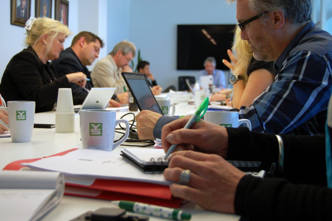 Kvinner og menn sitter rundt et bord og jobber. På bordet står kopper med logoen til YS.