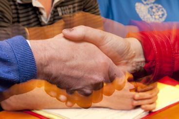 To personer gir hvarandre et håndtrykk.