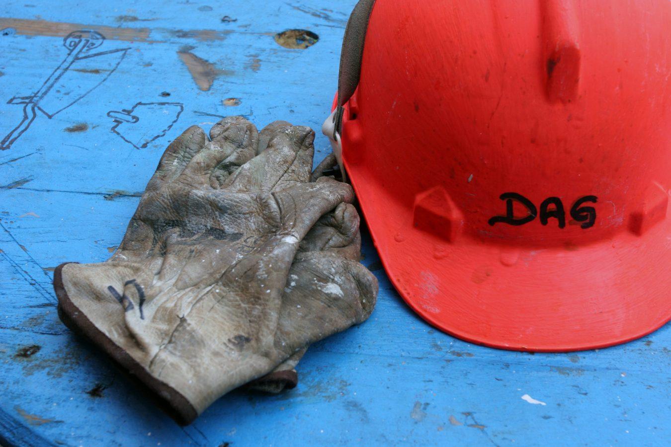 En rød hjelm ligger på et blått bord sammen med et par arbeidshansker.