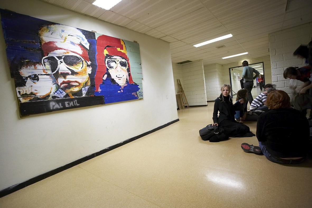 Ungsom sitter på et gulv i korridoren på en skole. Foto: Erik M. Sundt