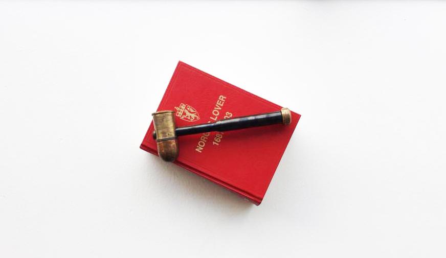 En klubbe ligger på en rød bok; Norges lover. Foto: Liv Hilde Hansen