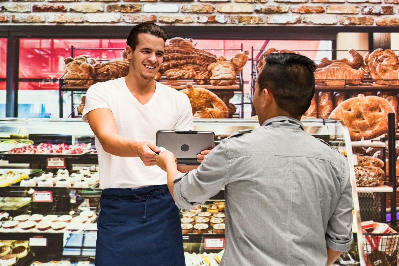 To unge menn står i et bakeri. Den ene gir en pc til den andre.