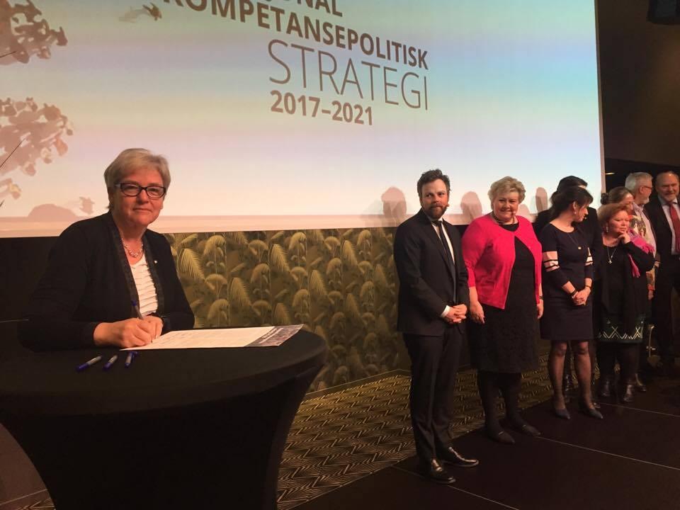 YS-leder Jorunn Berland står på scenen pg underskriver Nasjonal kompetansepolitsk strategi